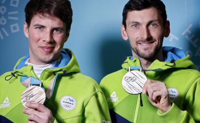 Slovenska junaka – Jakov Fak (desno) je s srebrom na posamični biatlonski preizkušnji na 20 km osvojil 20. slovensko kolajno na zimskih olimpijskih igrah, 21. je pripadla Žanu Koširju, bronastemu v deskarskem paralelnem veleslalomu. FOTO: Matej Družnik/Delo