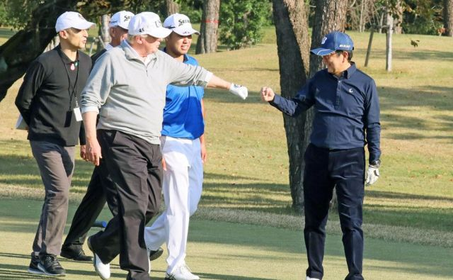 Donald Trump pozdravlja dobro potezo Šinza Abeja (desno) med njuno zadnjo partijo golfa. FOTO: Reuters