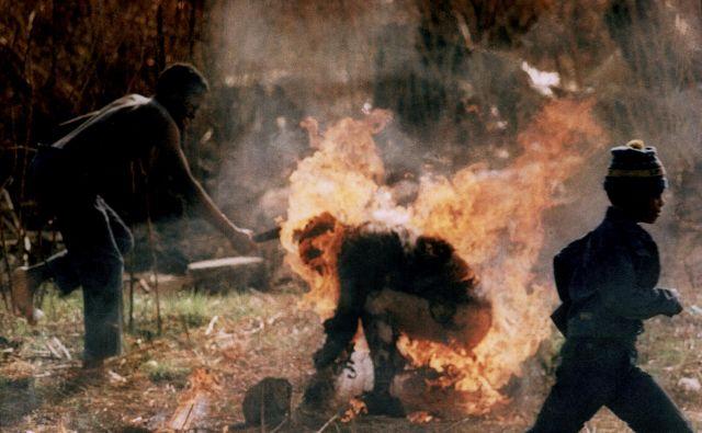 V spopadih med privrženci političnih strank Afriški nacionalni kongres (ANC) in Inkatha je v Južni Afriki leta 1990 umrlo več kot tri tisoč ljudi. Na fotografiji je pripadnik ANC z mačeto napadel gorečega pripadnika Inkathe. Greg Marinovich je za to fotografijo leta 1991 prejel Pulitzerjevo nagrado. FOTO: Greg Marinovich