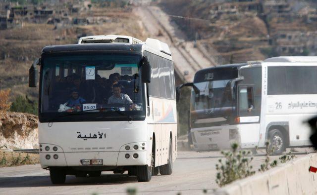 Uporniki in njihove družine zapuščajo mesto Rastan. FOTO: Omar Sanadiki/Reuters