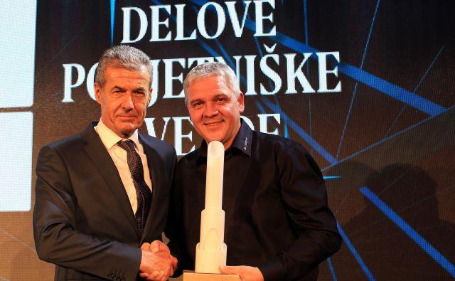 Katera podjetniška zvezda bo naslednila lanskega zmagovalca Dewesoft? Član žirije Stojan Petrič (levo) je lani podelil kipec za zmagovalca direktorju Dewesofta Andreju Orožnu.