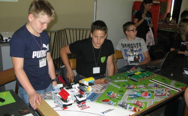 Jan, Blaž in Lovro, skupina Black Demons z OŠ Trbovlje, so predstavili robota iz pametnih legokock za zalivanje z vodo iz starih vodnjakov. FOTO: Polona Malovrh