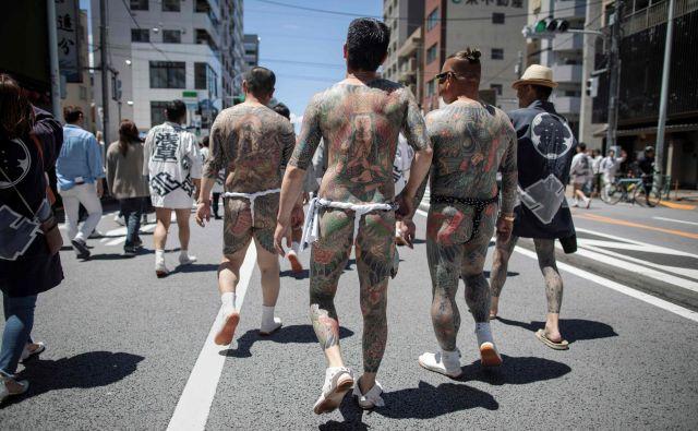 Jakuze s svojimi tradicionalnimi japonskimi tetovažami (irezumi), se sprehajajo po tokijskem okrožju Asakusa med letnim festivalom Sanja Matsuri. Tridnevni festival, ki ga obišče dva milijona Japoncev, je posvečen praznovanju treh ustanoviteljev templja Sensoji.FOTO: Behrouz Mehri/Afp