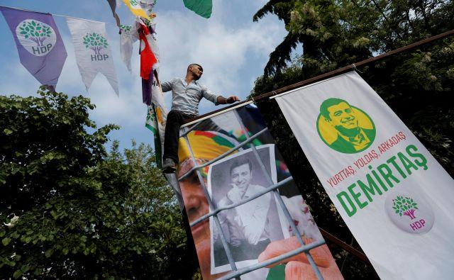 Podporniki kurdske Demokratične ljudske stranke obešajo plakate zaprtega sovoditelja stranke Selahattina Demirtaşa. FOTO: Reuters