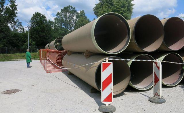 Kar 1200-milimetrske kanalizacijske cevi čakajo, da jih vgradijo v zemljo na Ljubljanskem polju. FOTO: Janez Petkovšek