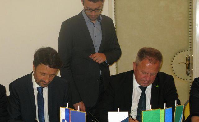 Predsedujoči razvojnega sveta zasavske regije Matjaž Švagan (levo) in gospodarski minister Zdravko Počivalšek podpisujeta dogovor za razvoj Zasavja. FOTO: Polona Malovrh/