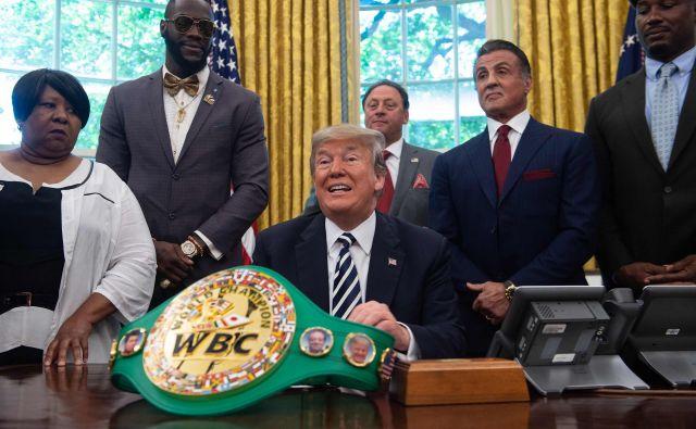 V Ovalni pisarni so se tako včeraj zbrali nekdanji in sedanji prvaki, ob ameriškem predsedniku je stal igralec <strong>Sylvester Stallone</strong>, eden od številnih znanih Američanov, ki so se leta zavzemali, da Bela hiša popravi dolgoletno krivico. FOTO: Nicholas Kamm/Afp