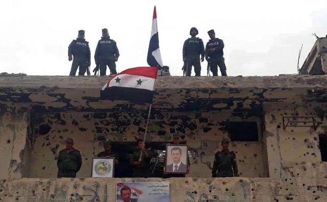 Sirski vojaki in policisti po zasedbi ene zadnjih utrdb Islamske države v bližini Damaska. FOTO: SANA via AP