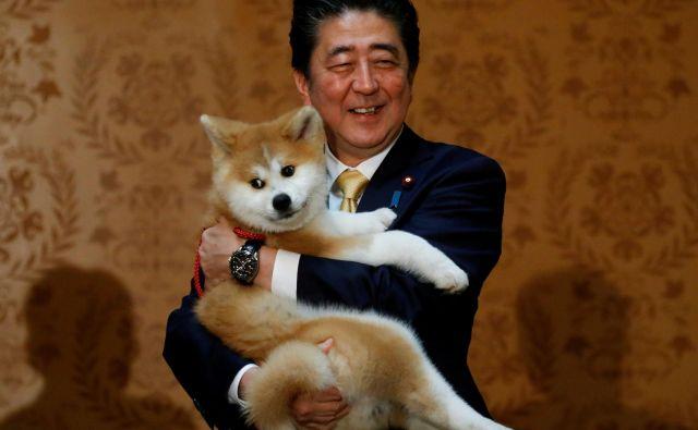 Portret japonskega premierja Shinza Abeja s psičkom pasme Akita Inu v Moskvi. Psička je podaril Rusinji Alini Zagitovi, umetnostni drsalki, ki je osvojila zlato medaljo. FOTO: Maxim Shemetov/Reuters