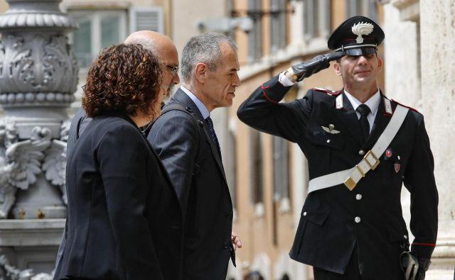Ekonomist Carlo Cottarelli (v sredini) težko računa na zaupanje parlamenta, karabinjer na straži pa mu salutira, kot bi že sestavil vlado, čas pa ni na strani Italije. FOTO: Giuseppe Lami/AP
