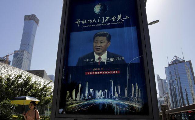 Mimoidoča v Pekingu na elektronskem zaslonu posluša govor predsednika Xi Jinpinga o nujnosti krepitve kitajske samozadostnosti na področju elektronike. FOTO: AP