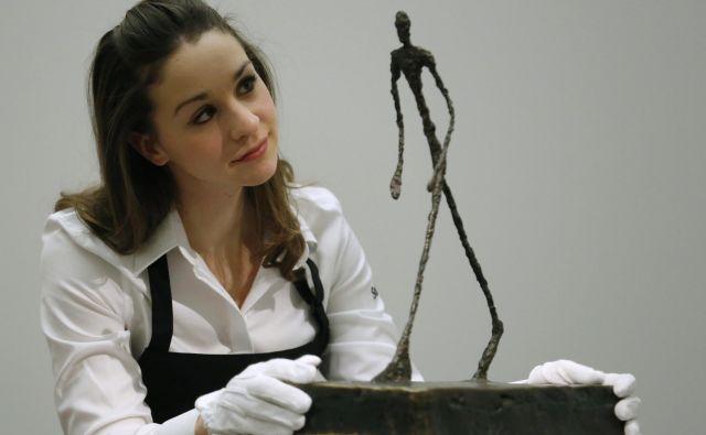 Ena zaposlenih pri Sotheby's ob kipcu Alberta Giacomettija pred dražbo v Londonu. FOTO: Reuters Reuters