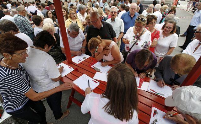 Med slovesnostjo na Vidovo nedeljo so pred cerkvijo Sv. Vida v Šentvidu, podpisovali peticijio proti nameri župana Jankovića, da občina prevzame pokopališče. FOTO: Matej Družnik