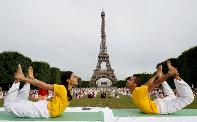 Pred prihajajočim mednarodnim dnevom joge 21. junija se po vsem svetu izvajajo brezplačneseanse joge na prostem. Utrinek izvajanja joge na travniku pred Eifflovim stolpom v Parizu.FOTO: Francois Guillot/AFP