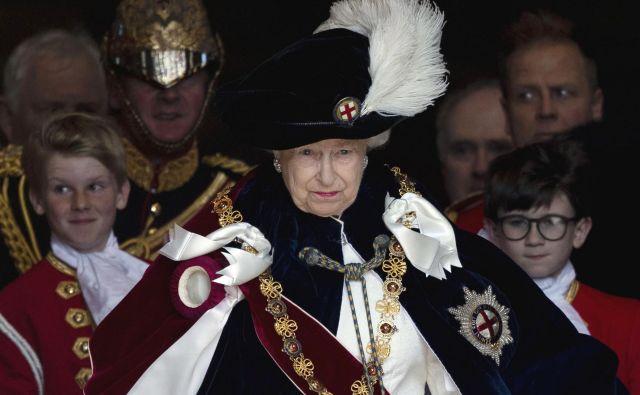Portret kraljice Elizabete II. pred kapelo sv. Jurija v Windsorju, kjer je potekala slovesnost najstarejšega plemenitega reda britanske cerkve. Najstarejši cerkveni red viteštva v Veliki Britaniji je ustanovil kralj Edward III. pred skoraj 700 leti.FOTO: Steve Parsons/AFP