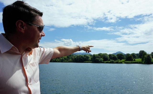 Velenjski podžupan Peter Dermol kaže, kje na Velenjskem jezeru angleški investitor načrtuje hotel na vodi.