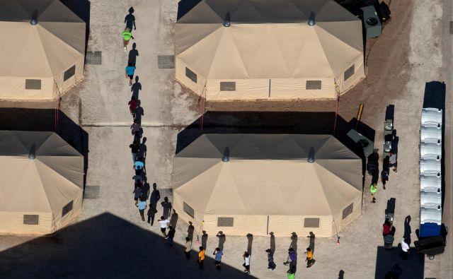 V objektu za pridržanje ob mehiški meji v teksaškem mestu Tornillo osebje vodi otroke priseljencev med šotori do prostora, v katerem strežejo hrano. FOTO: Mike Blake/Reuters