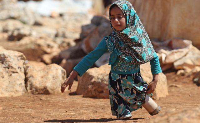 Portret osemletne sirske deklice Maye Mohammad Ali Merhi, ki se je rodila brez spodnjih udov. Ker ji družina ni mogla privoščiti pravih protetičnih udov, jih je oče naredil kar iz pločevink, napolnjenih z bombažem in ostankov krp. Njena družina je morala zaradi vojne zapustiti Alep. FOTO: Aref Vatad/AFP