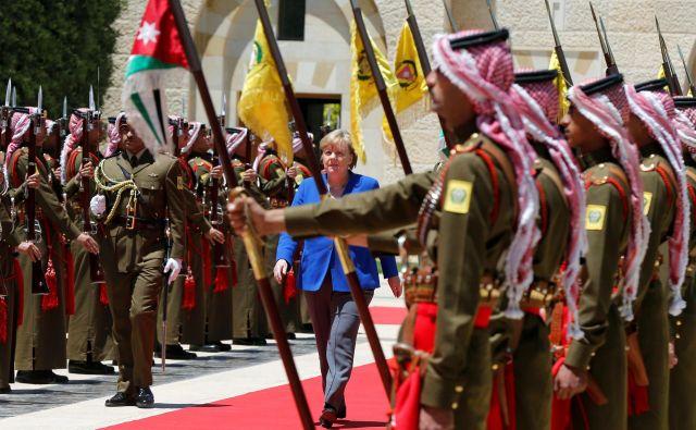 Kanclerka Angela Merkel med pregledom častne straže v kraljevi palači v Amanu . FOTO: Reuters