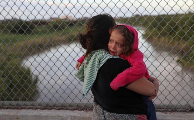Begunka iz Hondurasa s triletno hčerjo v negotovosti čaka na mostu Brownsville & Matamoros blizu Brownsvilla v Teksasu ob meji z Mehiko, potem ko so ji ameriške oblasti prepovedale vstop v ZDA. FOTO: Reuters