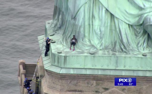 Turisti so morali zapustiti kip, medtem ko je ženska vztrajala pri nogah simbola svobode. FOTO: AP