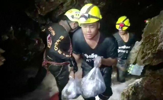 Reševalci v jamo nosijo potrebščine tako za otroke kot za reševalce. FOTO: Reuters