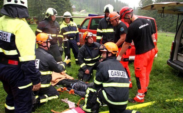 Gasilci in reševalci z roko v roki pomagajo poškodovanim. FOTO: Jože Miklavc