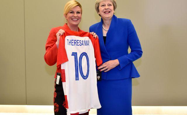 Pred polfinalnim dvobojem na SP med Hrvaško in Anglijo je hrvaška predsednica Kolinda Grabar-Kitarović (levo) britanski premierki Theresi May na vrhu Nata v Bruslju podarila hrvaški dres s številko 10. FOTO: AFP