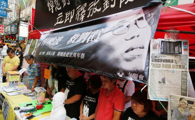 Prodemokratski aktivisti so se v Hongkongu z minuto molka spomnili Liu Xiaoboja in proslavili odhod njegove vdove Liu Xia na svobodo v Berlin. FOTO: Reuters