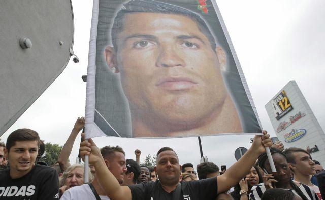 Juventusovi navijači so svojega novega junaka Cristiana Ronalda pričakali pred štadionom, kjer so tudi dvignli plakat z njegovo podobo. Foto AP
