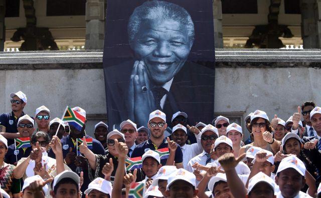 Člani južnoafriške reprezentance kriketa na slovesnosti ob 100. obletnici rojstva Mandele pozirajo z otroki. FOTO: Ishara S. Kodikara/AFP