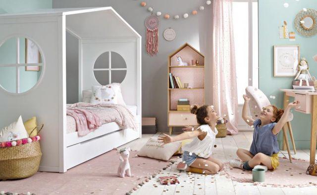 Postelja na fotografiji ima polno streho in stranici, na katerih sta okrogli okni. Prav ti dajeta poseben pečat beli hiški.