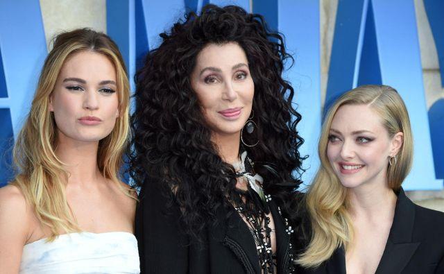 """Igralke in pevke Lily James, Cher in Amanda Seyfried na rdeči preprogi ob prihodu na svetovno premiero filma """"Mamma Mia! Here We Go Again"""" v Londonu. Vse tri imajo v novem muziklu glavne vloge.Foto - Afp"""