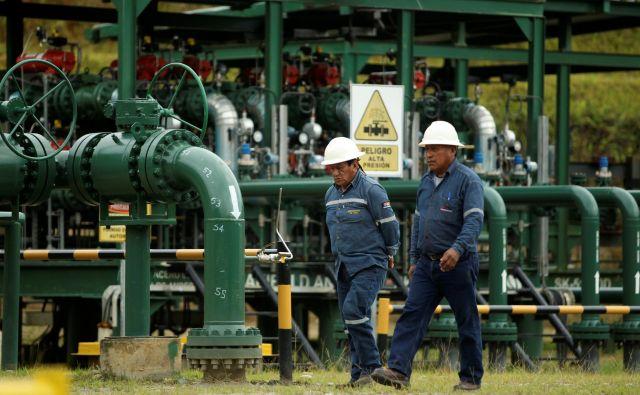 Uslužbenca državnega naftnega podjetja Petroamazonas blizu nacionalnega parka Yasuní, kjer so začeli črpati nafto pred dvema letoma. FOTO: Reuters