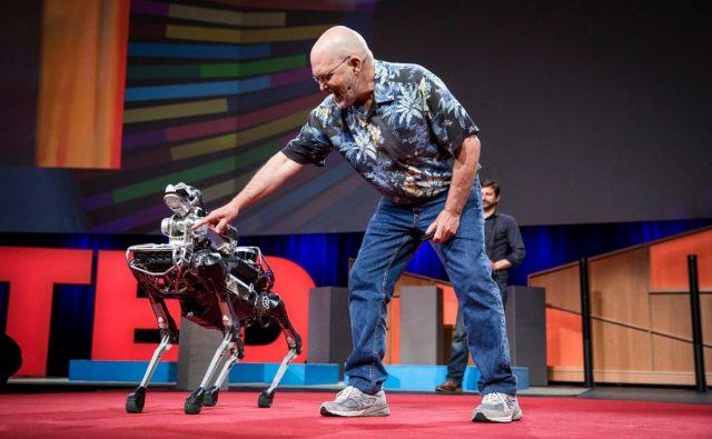 Marc Raibert ukazuje SpotMiniju, naj sede. FOTO: Boston Dynamics