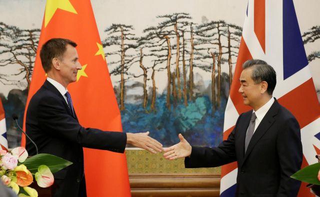 Kitajski zunanji minister Wang Yi si ni vzel k srcu prvega spodrsljaja britanskega zunanjega ministra Jeremyja Hunta (levo). FOTO: Reuters