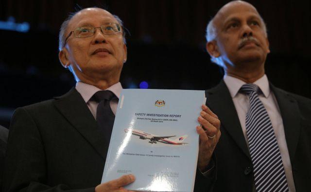 Glavni preiskovalec Kok Soo Chon (desno) v roki drži poročilo o izginulem malezijskem letalu MS370, ki obsega 495 strani. FOTO: Reuters