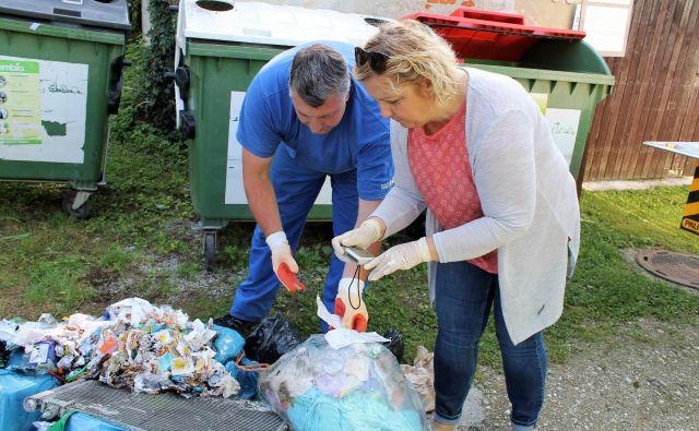 Delavec Simbia in inšpektorica Nataša Kos med brskanjem po odpadkih na Dobrni. FOTO: Simbio