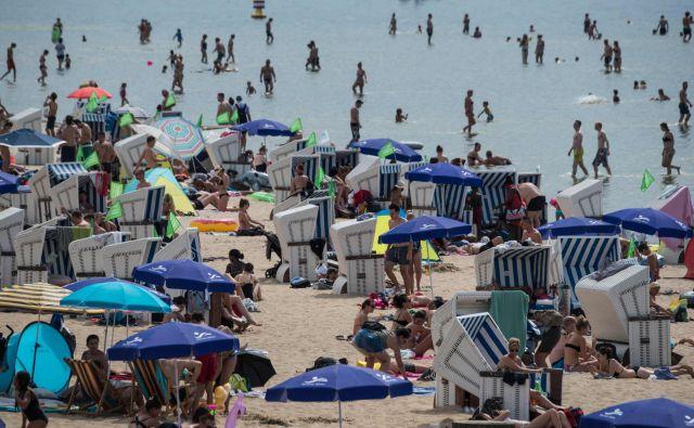 Natrpane nemške plaže, na katerih ljudje iščejo senco in ohladitev. FOTO: Afp