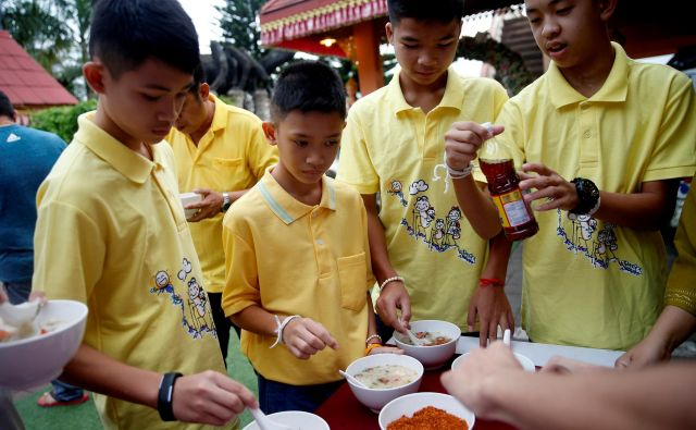 11 od 12 rešenih tajskih dečkov jev znak zahvale vstopilo v samostan, ki so ga zapustili v soboto.FOTO: Soe Zeya Tun/Reuters