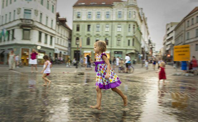 Na Prešernovem trgu v Ljubljani, kjer se v umetnem dežju lahko ljudje malo ohladijo. Foto Voranc Vogel