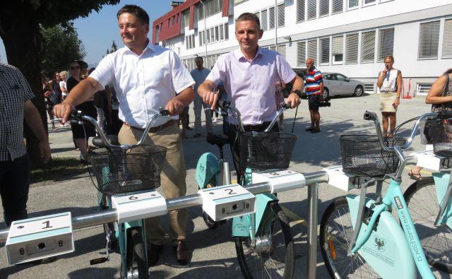 Župan Boštjan Trilar in direktor Elektra Gorenjska Ivan Šmon sta prva uporabila novo električno postajo za izposojo koles. Foto Blaž Račič