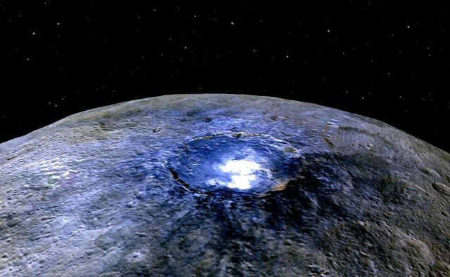 Površje Cerere je večinoma črno kot asfalt, a se ponaša tudi z okoli 130 svetlimi pegami. Znanstveniki domnevajo, da gre za mineralne snovi ali pa z amonijakom bogate gline. Svetlika se tudi, na tej sliki sicer umetno obarvan, krater Occator. FOTO: Nasa
