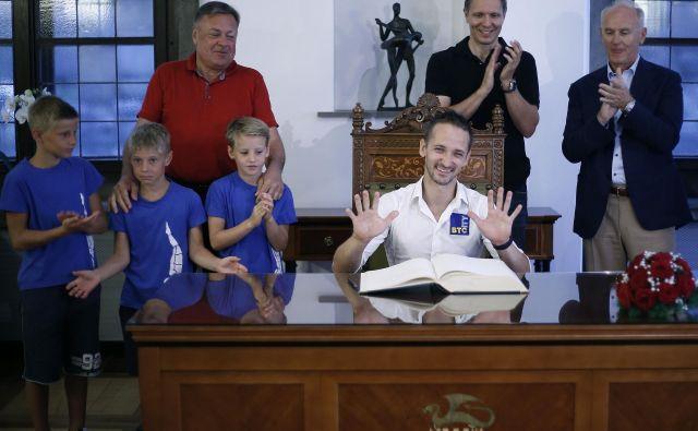 Sašo Bertoncelj se je dan po prihodu z evropskega prvenstva v ljubljanski Mestni hiši vpisal v spominsko knjigo, kar je označil za zelo zahtevno nalogo. Foto Blaž Samec/Delo