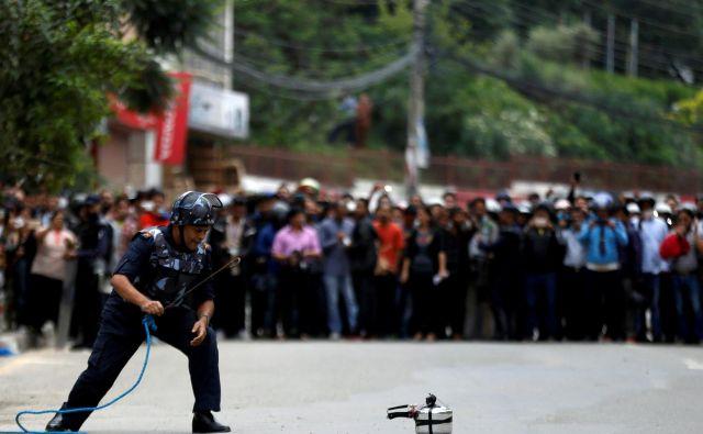 Nepalski policist po vsesplošnem preplahu v Lalipurju preverja pritisk v domnevni bombi. Pozneje se je pokazalo, da je bil lažni alarm. FOTO: Naveš Čitrakar/Reuters