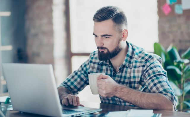 Concept of having a break at work. Concentrated calm peaceful serious office worker watching carefully a video on the internet using his laptop and drinking tea Foto Getty Images/istockphoto Getty Images/istockphoto