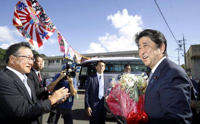 Japonski premier Šinzo Abe je dobil šopek cvetja, ko je sporočil, da bo še tretjič kandidiral za predsednika vladajoče Liberalnodemokratske stranke. FOTO: Reuters