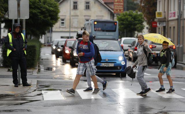 Policisti opozarjajo starše, naj otroke pred prihodom v šolo naučijo spoznati barve na semaforju in pravilno prečkati cesto. FOTO: Leon Vidic/Delo