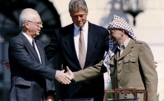 Pred četrt stoletja sta vodja Palestinske osvobodilne organizacije Jaser Arafat in predsednik izraelske vlade Jicak Rabin »pod patronatom« ameriškega predsednika Billa Clintona pred Belo hišo podpisala zgodovinski sporazum iz Osla. Foto Reuters
