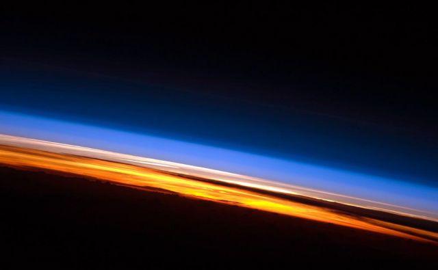 Na tej fotografiji sončnega zahoda, posnetega z Mednarodne vesoljske postaje, so jasno vidne tri plasti atmosfere: troposfera se sveti oranžno, stratosfera, kjer se najaha ozon, je roza, višje plasti so modrikaste. FOTO: Nasa